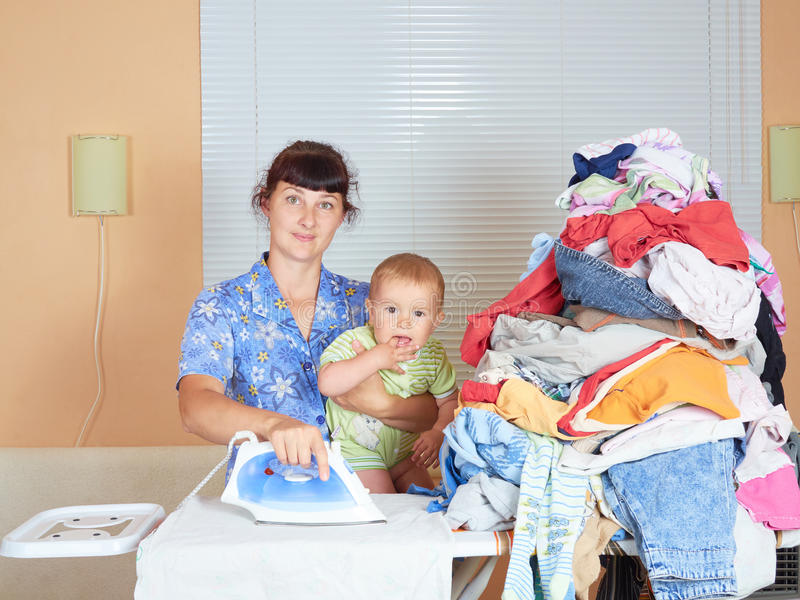 Mother holding baby in arm, ironing with the other arm. royalty free stock photography