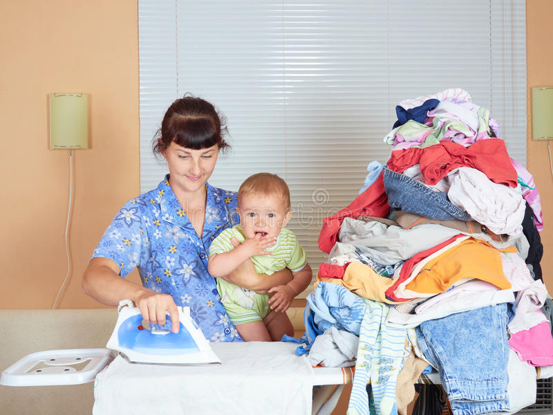 Mother holding baby in arm, ironing with the other arm. royalty free stock photo