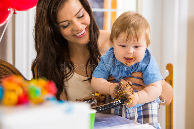 Mother Holding Baby Boy Eating Cupcake stock images