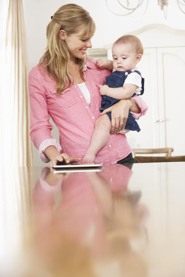 Mother Holding Baby Daughter Whilst Using Digital Tablet stock photo