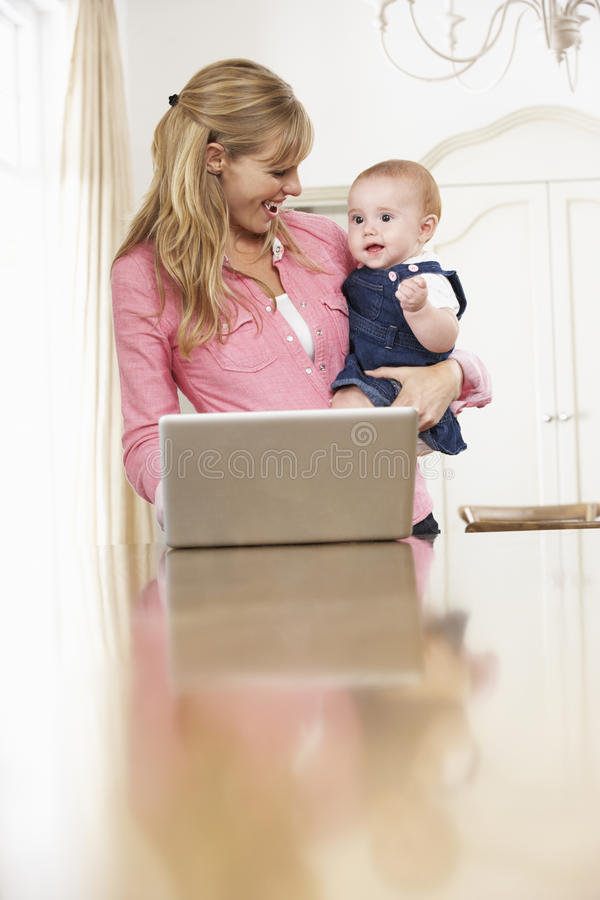 Mother Holding Baby Daughter Whilst Using Laptop stock photo