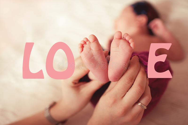 Mother holding baby feet royalty free stock photography