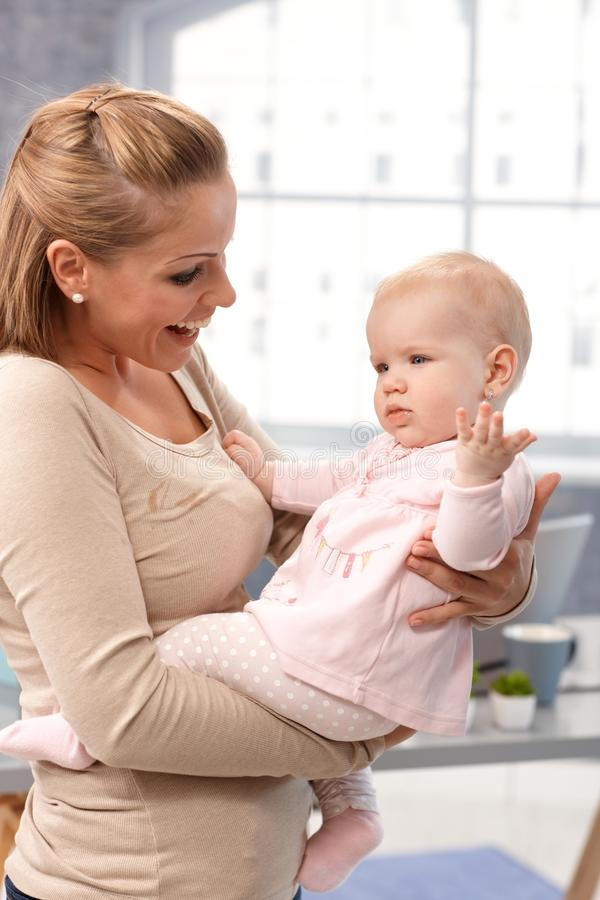 Mother holding baby girl in arms playing royalty free stock photo