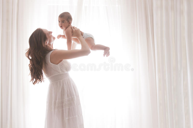 Mother Holding Baby Son By White Curtains royalty free stock photography