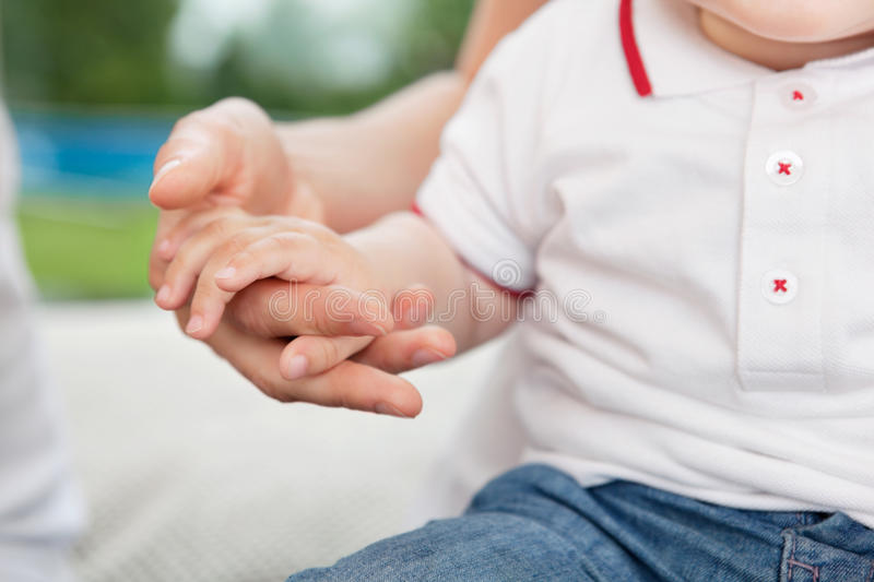 Mother holding child's hand stock image