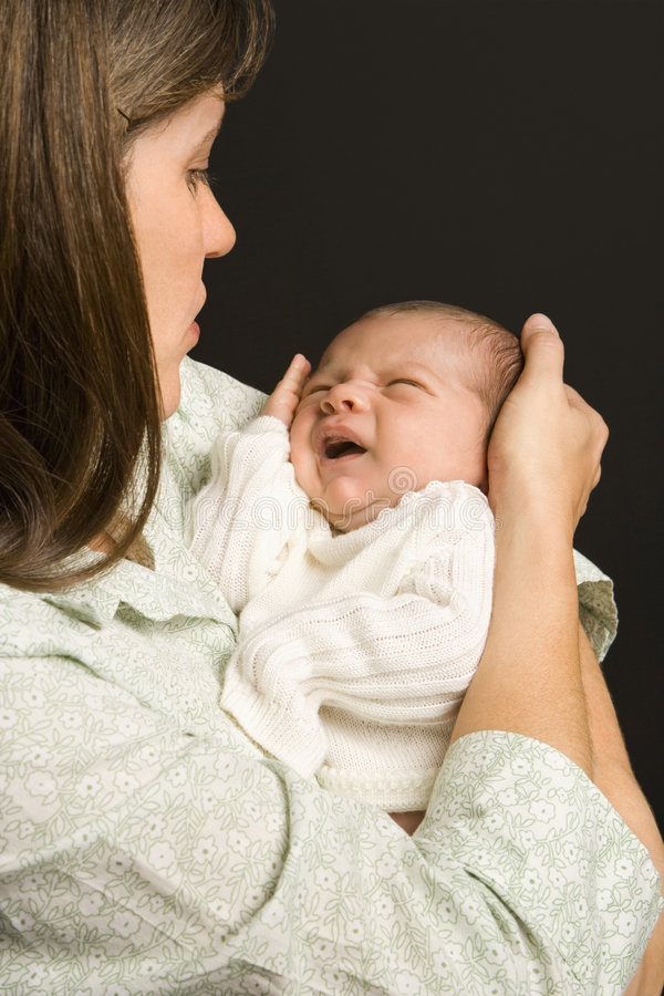 Mother holding crying baby. stock photo