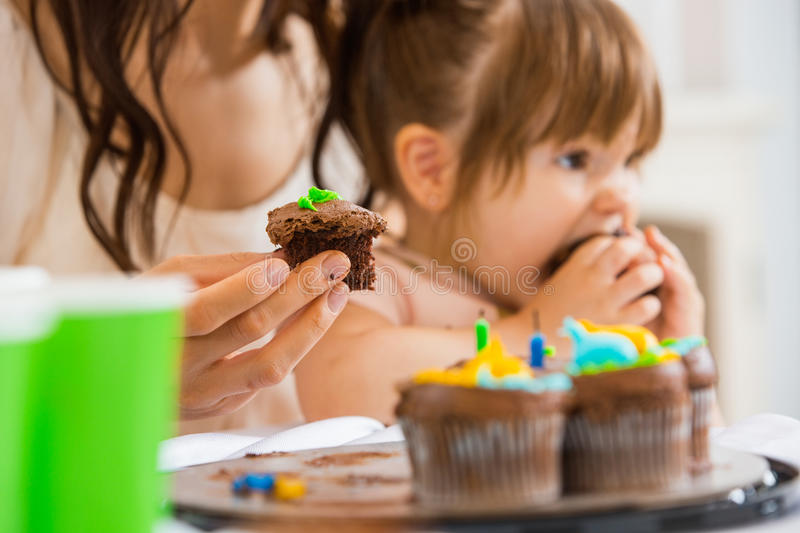 Mother Holding Cupcake With Girl Eating Cake stock photo