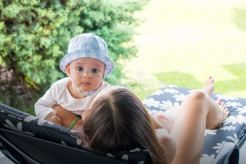 Mother holding curious baby boy with beautiful face in hat while lays on flower pattern deck chair stock photo