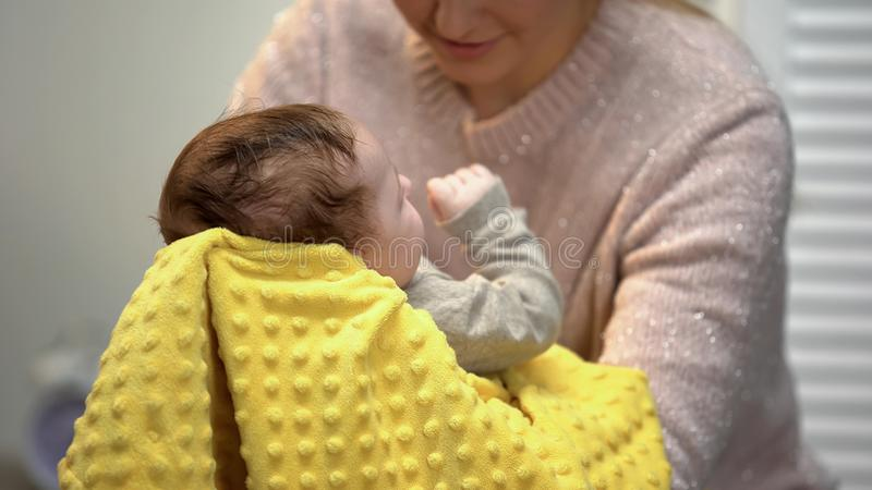 Mother holding cute baby vertically after feeding, newborn burping techniques. Stock photo royalty free stock image