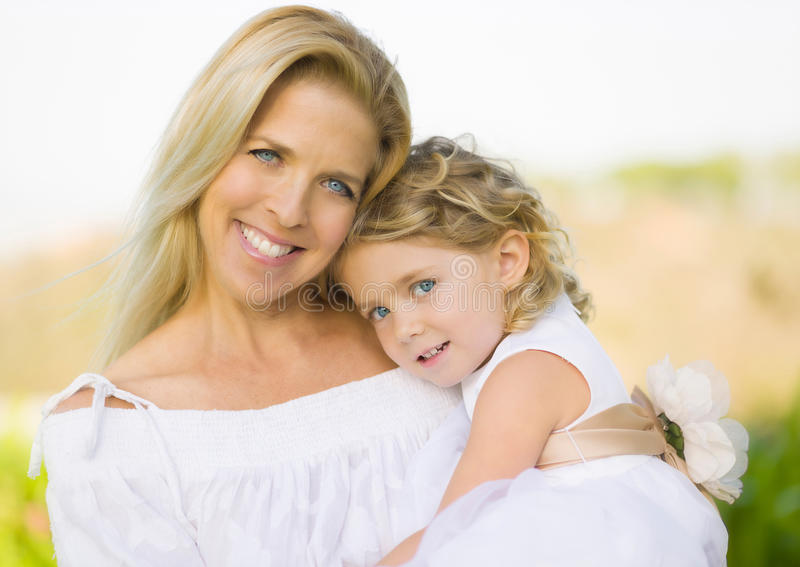 Mother Holding Daughter Flower GIrl. A smiling, happy blue-eyed mother with a white dress and long blond hair closely and lovingly holds her pretty, young, blue stock photos