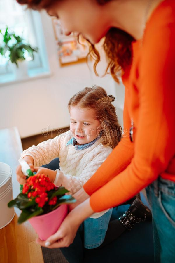 Mother holding flowerpot while daughter watering nice flowers. Mother holding flowerpot. Red-haired mother holding flowerpot while daughter watering nice flowers stock photos