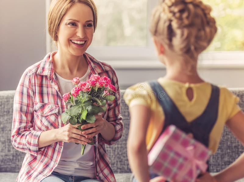 Mother Holding Flowers and Looking at Her Daughter. stock photography