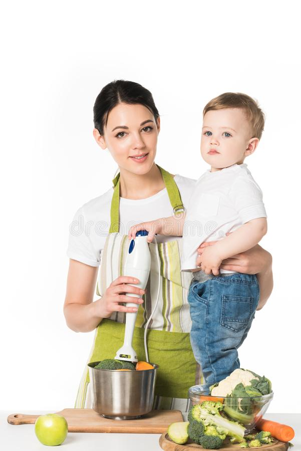 mother holding hand blender and son standing on table with ingredients stock photography