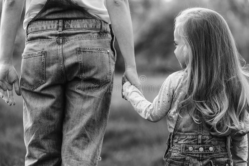 Mother holding a hand of her daughter in spring day outdoors royalty free stock photos