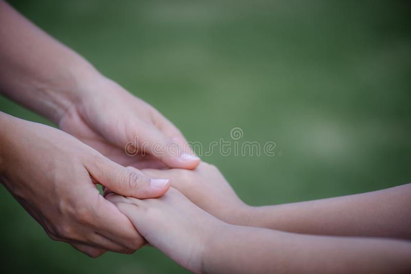 Mother holding a hand of his son with green glass background stock photos