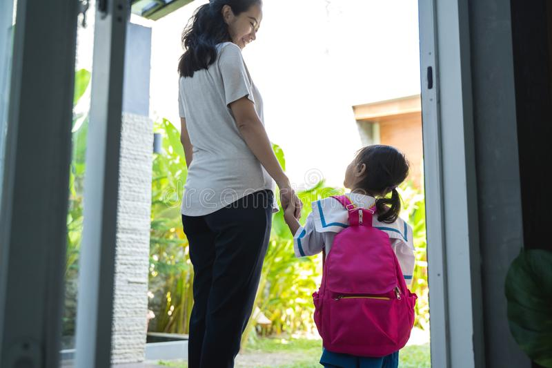 Mother holding hand of little daughter with backpack stock image