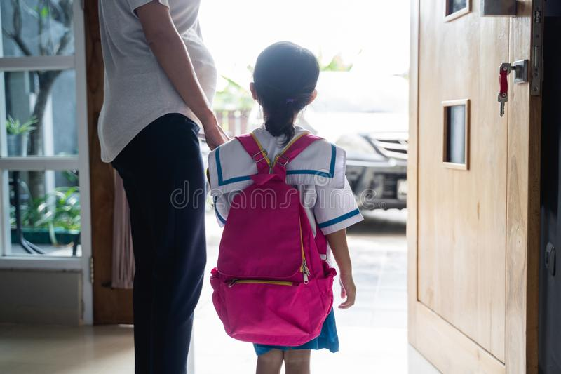 Mother holding hand of little daughter with backpack stock photography