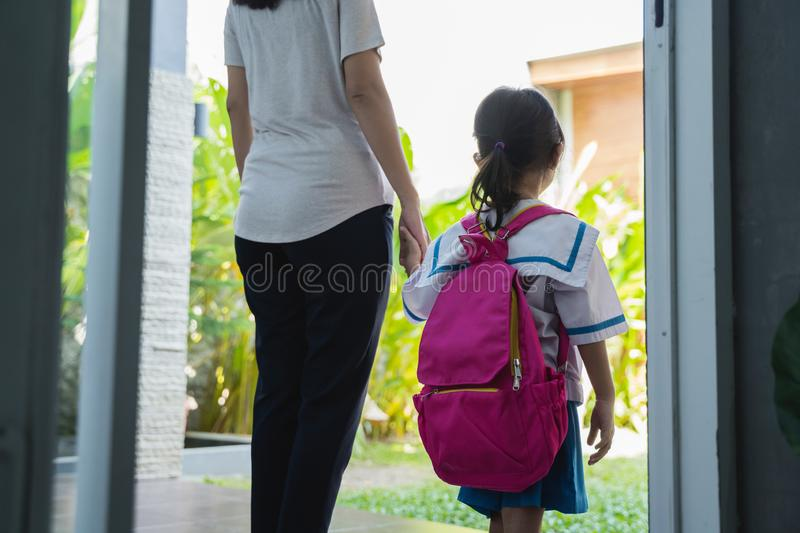 Mother holding hand of little daughter with backpack royalty free stock images