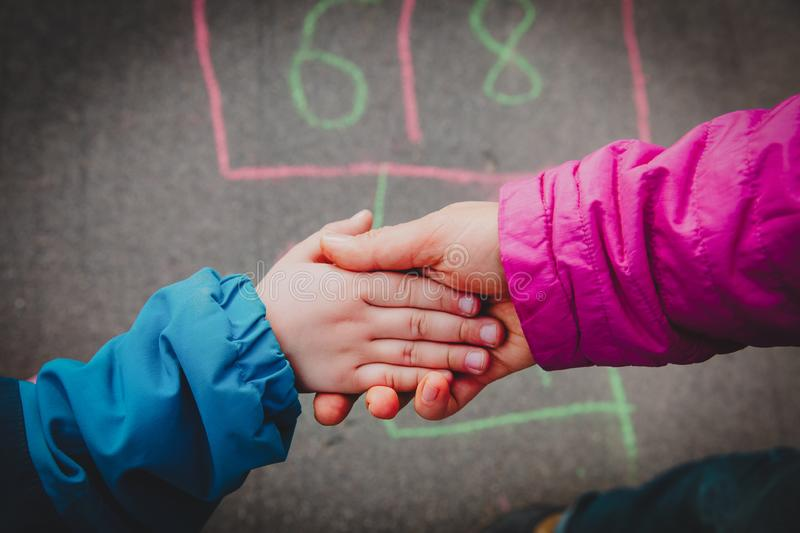 Mother holding hand of little daughter on playground, parenting stock photo