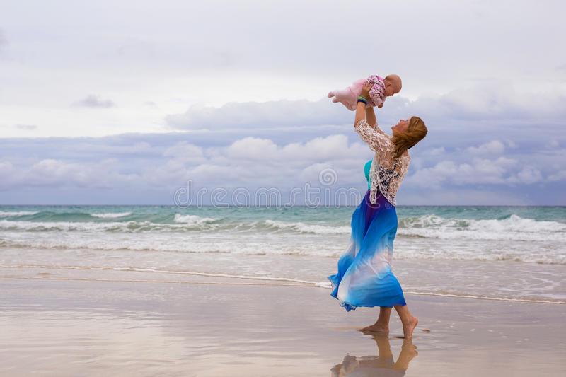Mother holding her baby on the beach stock photography