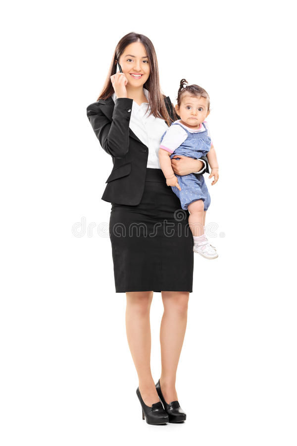 Mother holding her daughter and talking on phone stock photo