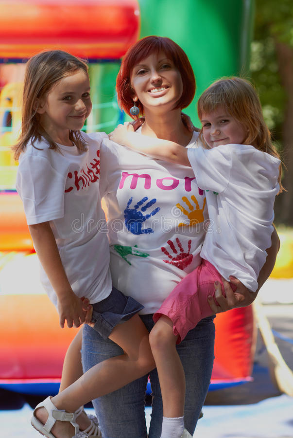 Mother holding her daughters in arms outdoors royalty free stock photos
