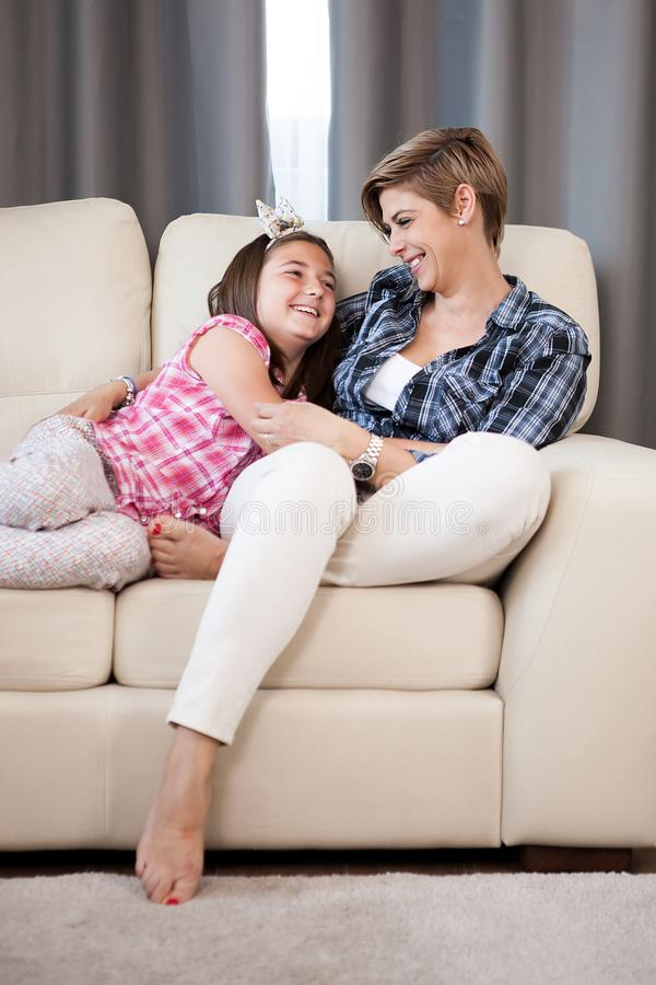 Mother holding her teenage daughter in her arms. On the couch in the living room smiling at each other royalty free stock photo