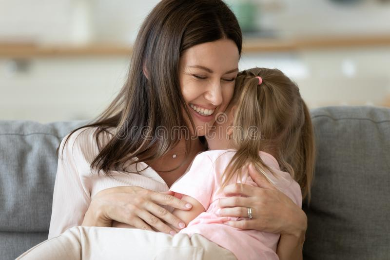 Mother holding on lap daughter embraces her enjoy tender moment royalty free stock image