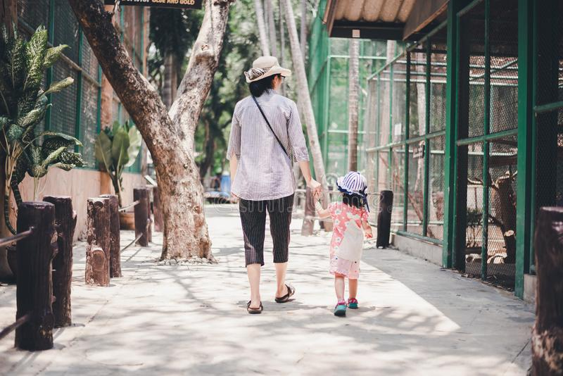 Mother holding little child hand and walking to see animals. Mother holding little child hand and walking in the zoo to see animals stock photo