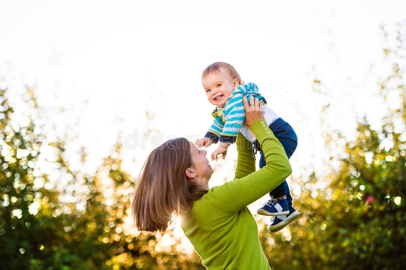 Mother holding little son, throwing him in the air royalty free stock photography