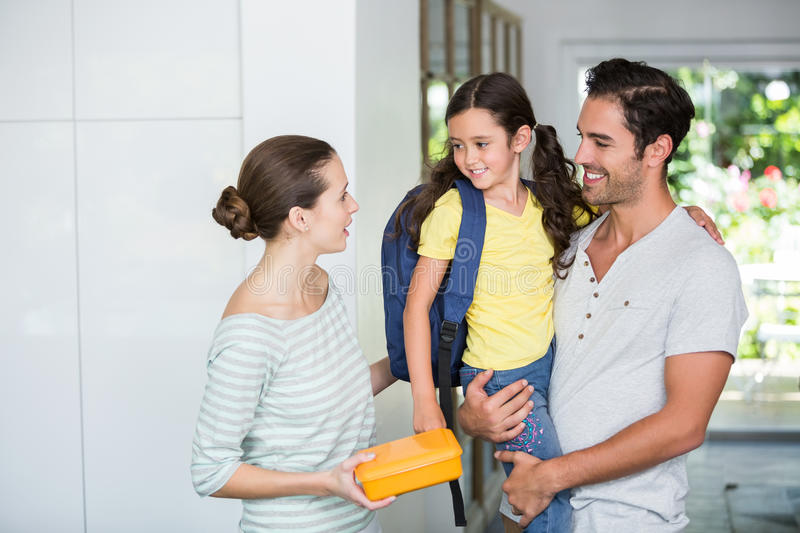 Mother holding lunch box with father carrying daughter. At home stock photo