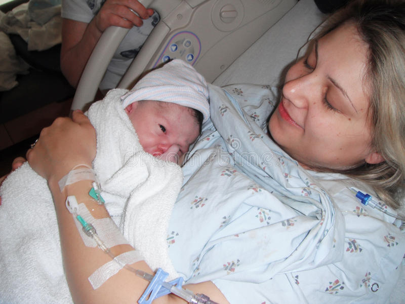 Mother holding newborn baby after delivery stock photos