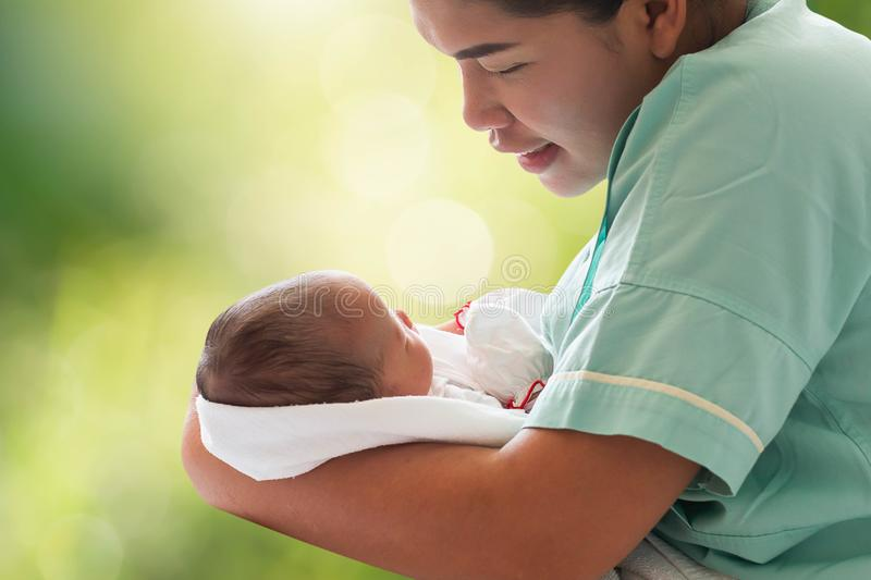 Mother holding newborn infant baby girl in arm on blurred bokeh royalty free stock photography