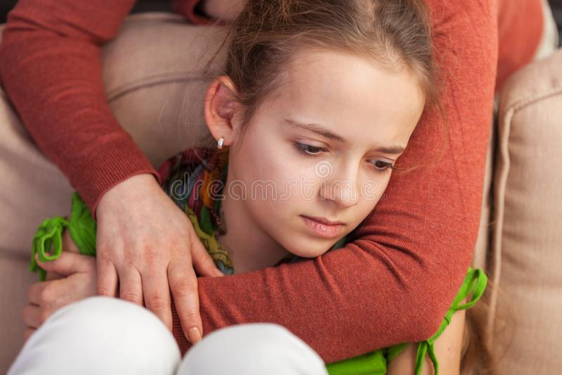 Mother holding sad teenager girl from behind - close up royalty free stock photography