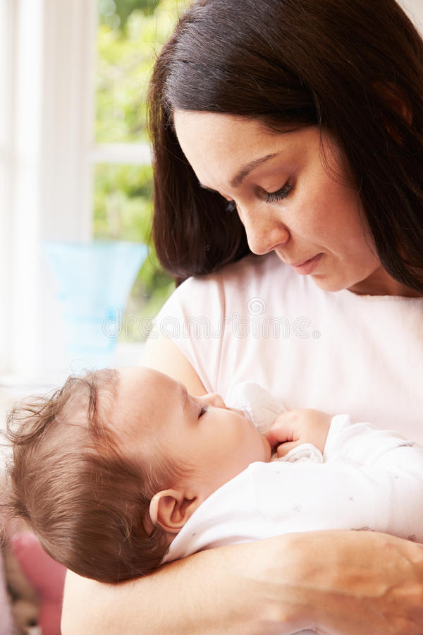 Mother Holding Sleeping Baby Boy At Home royalty free stock photo