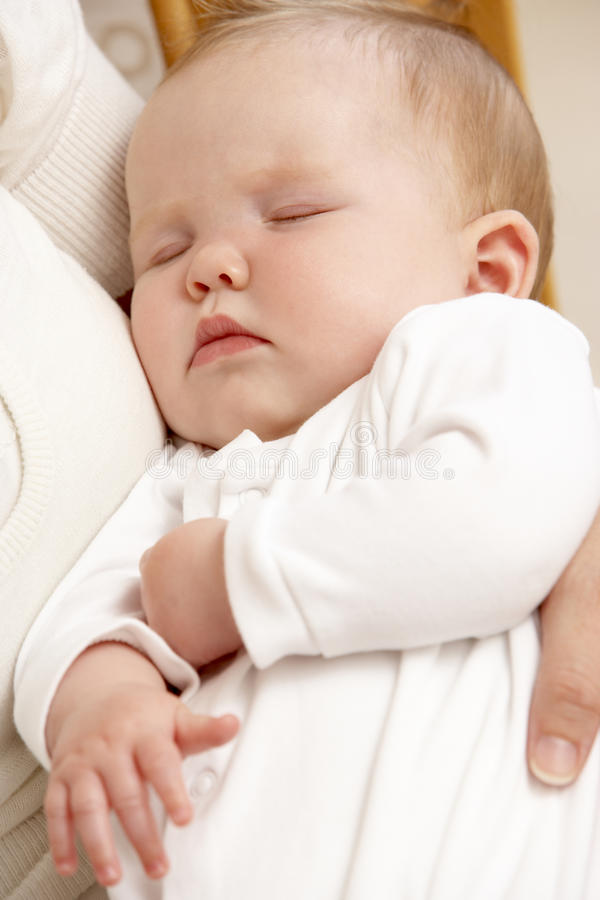 Mother Holding Sleeping Baby In Nursery. Close up of Mother Holding Sleeping Baby In Nursery royalty free stock images