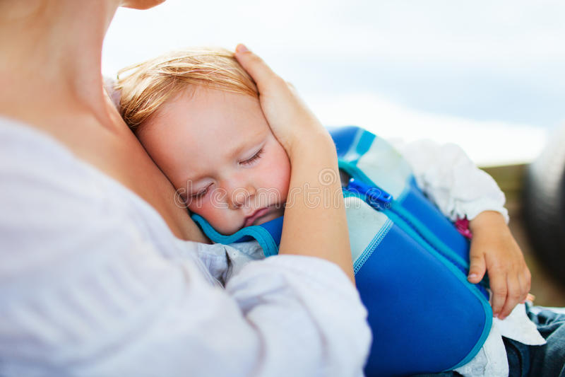 Mother holding sleeping daughter. Mother holding her sleeping toddler daughter at airport while traveling on boat stock photography
