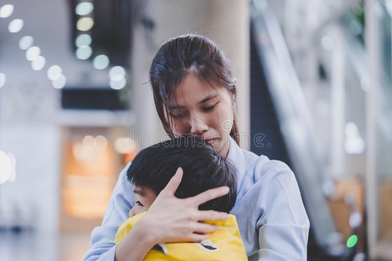 Mother holding an upset boy closely stock images