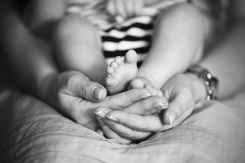Mother holds baby feet in hands stock image
