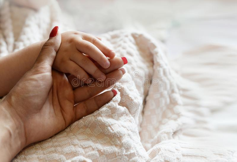 Mother holds the hand of a newborn royalty free stock photography