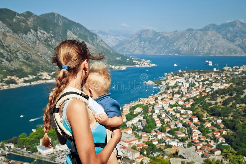 Mother holds her son in her hands on top of mountain and looks at the Bay of Kotor in Montenegro. Rear view royalty free stock photo