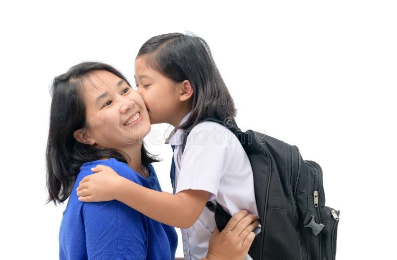 Mother hug and kiss cute girl student stock photo