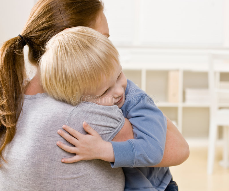 Mother hugging and comforting her son stock photography