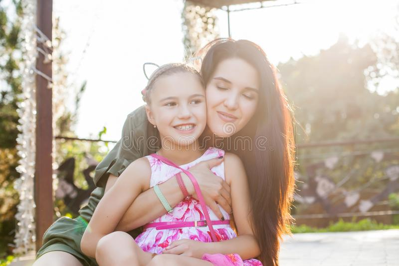 Mother hugging daughter with closen eyes. Attractive mother hugging daughter with closen eyes. Daughter smiling. Concept of happy loving family royalty free stock images