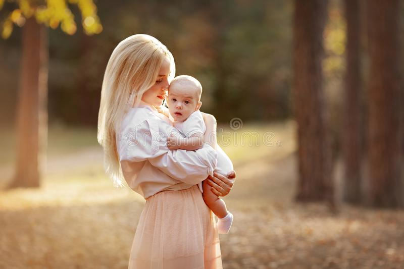 Mother Hugging her Baby. Autumn landscape. Walk in nature outdoors. Family, motherhood, parenting and child care concept. Young royalty free stock image
