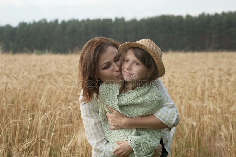 Mother hugging her little daughter, wheat field background stock image