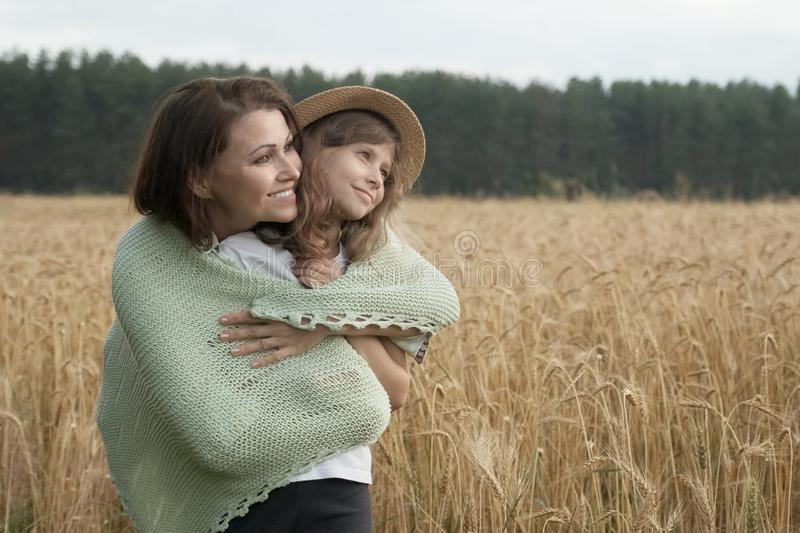 Mother hugging her little daughter, wheat field background stock photo