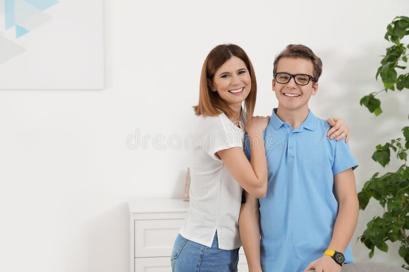 Mother hugging her teenager son stock photo