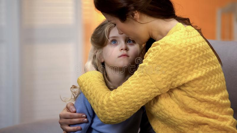 Mother hugging sad little adorable girl home after work, family love and care stock photography