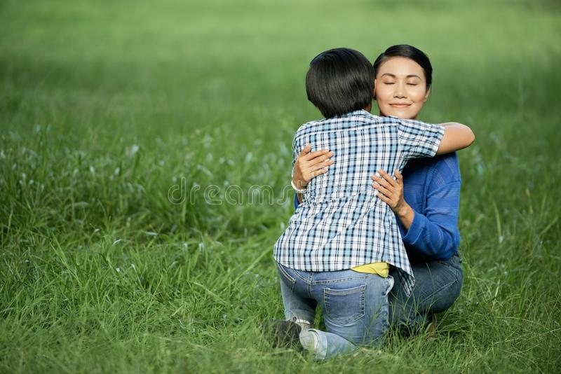 Mother hugging son. Happy mature Vietnamese woman sitting on grass in park and hugging her teenage son royalty free stock image
